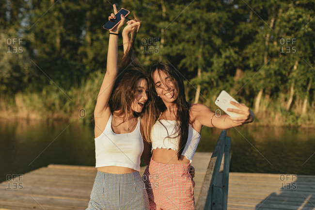 Two friends taking silly selfies by a lake