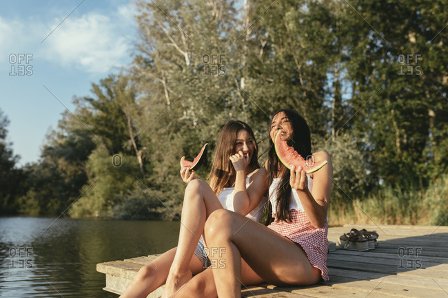 Friends eating watermelon on a lake and laughing