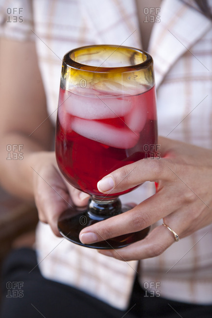 Woman holding sorrel cocktail with ice