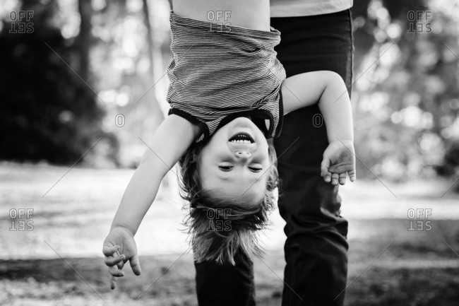 Father holding son upside down in black and white