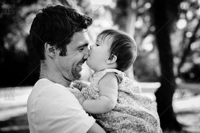 Baby girl sucking daddy's nose in black and white