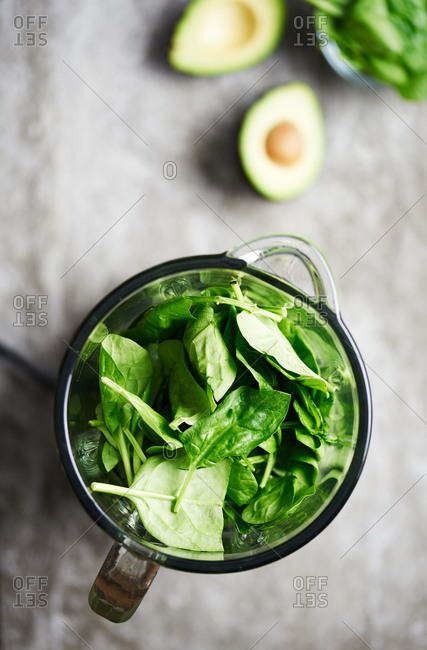 Making a healthy green spinach smoothie in a blender