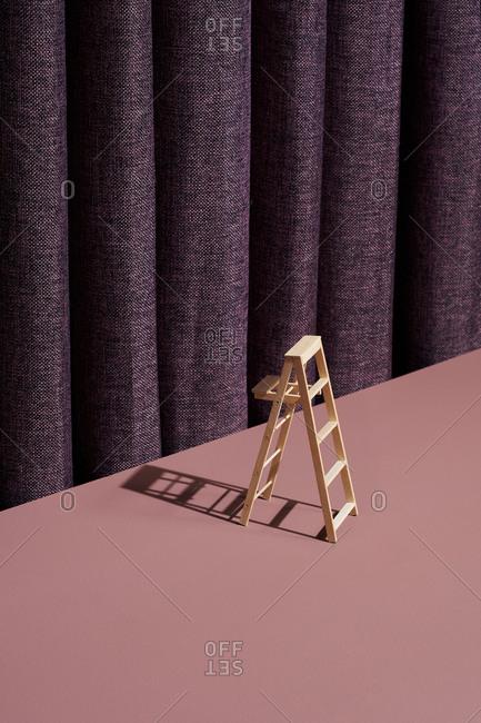 Wooden ladder on purple background