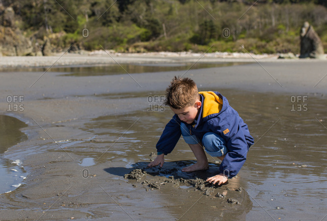 Boy digs in sand at Ruby Beach, Washington