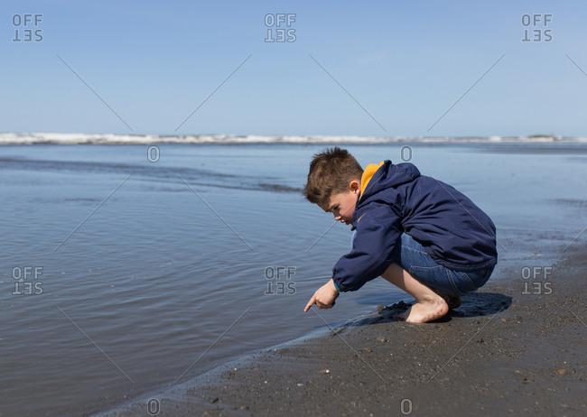 Boy explores the shore at Ruby Beach, Washington