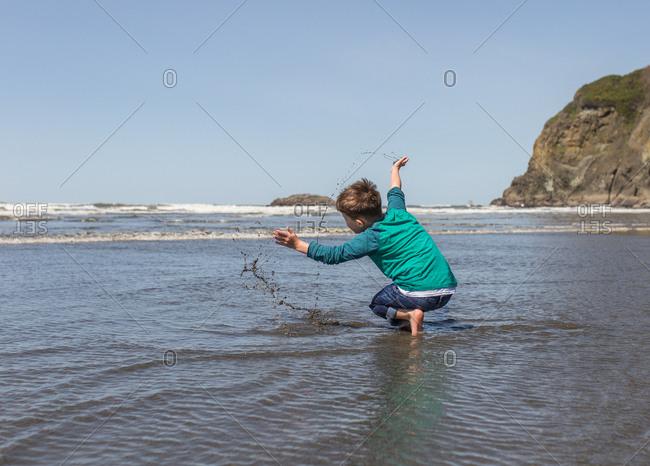 Boy splashes in muddy water at Ruby Beach, Washington