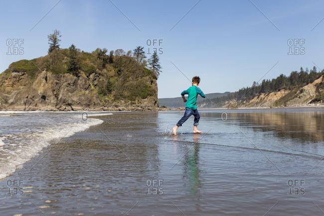 Boy plays in the surf at Ruby Beach, Washington