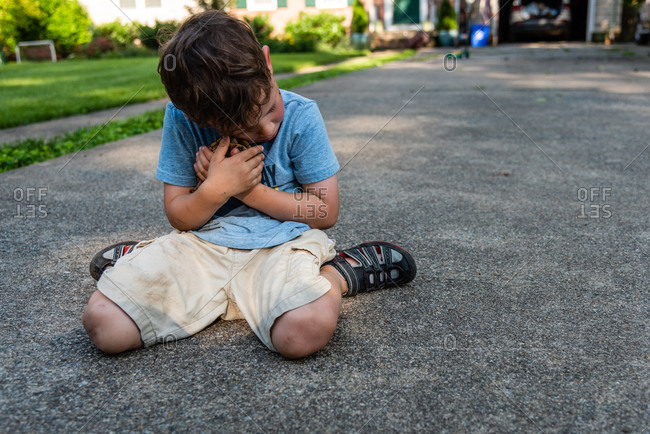 Sad Little boy kneeling on ground saying goodbye and cuddling pet eastern box turtle