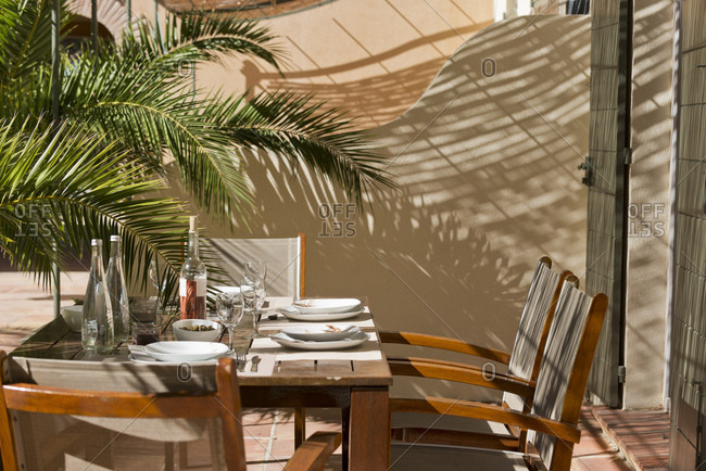 Ramatuelle, France - September 18, 2013: Set table and palm tree on patio under pergola