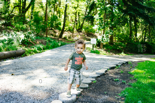 Little boy walking along the side of a footpath in a public garden