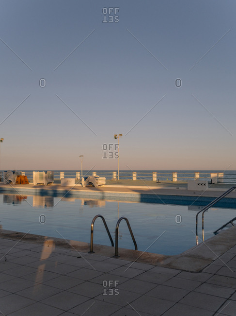 Corner of oceanfront swimming pool at sunset