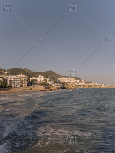 Distant view of beach town across shallow tide