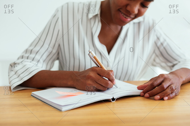 Close-up of a woman writing on notebook in office
