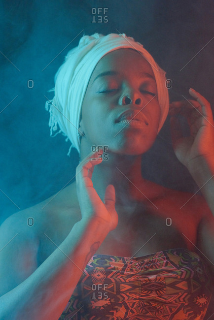Waist-up portrait of young beautiful Black woman in swimsuit and head wrap posing in fog with her eyes closed on dark background