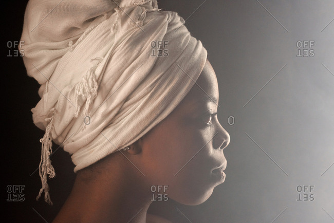 Profile portrait of attractive African American woman wearing white turban looking into the distance in fog on dark background