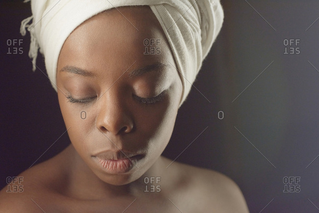 Portrait of Black Beauty. Headshot of young beautiful African woman in white turban with bare shoulders looking down on dark background