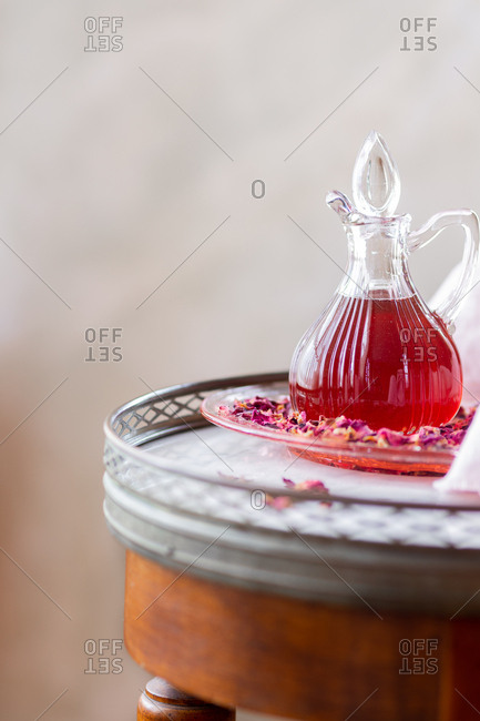 Glass server of rose syrup arranged with rose petals on marble table