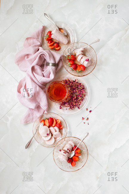 Top down view of bowls of strawberries and Indian kulfi served with rose syrup