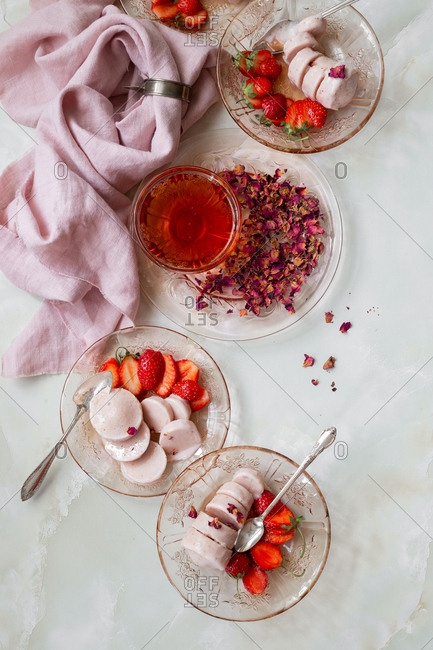 Overhead view of juicy strawberries and Indian kulfi served with rose syrup