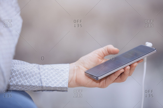 Hands of young woman selecting music on smartphone