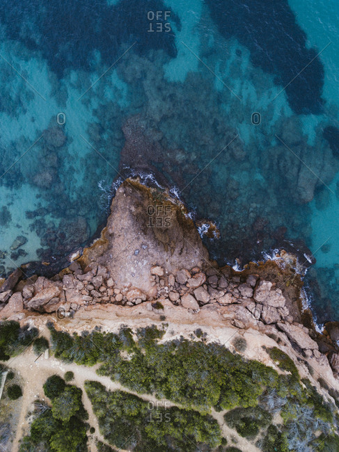 Scenic footpaths on rocky Cala Vidre beach from above