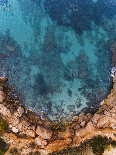 Top view of water and rocks on curved Spanish coastline