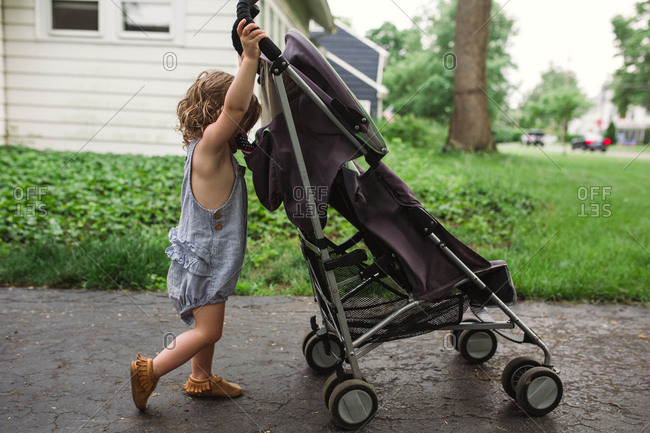 Toddler girl pushes empty baby stroller in driveway