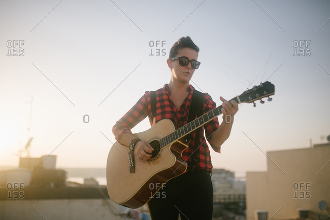 Young woman playing guitar at the rooftop