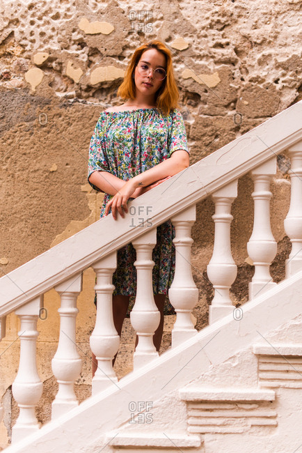 Young redheaded woman standing on staircase