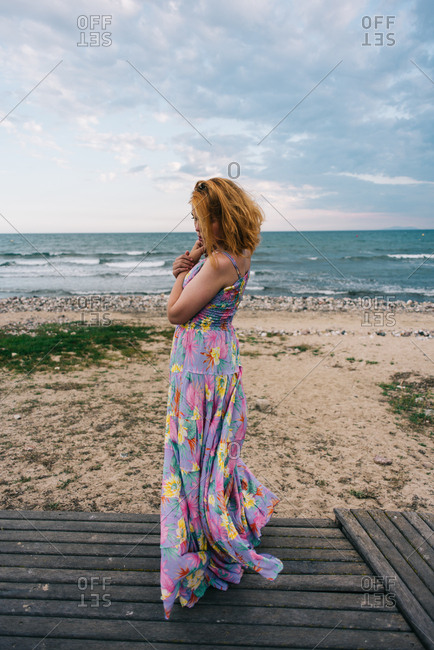 Young redheaded woman wearing colorful dress standing near sandy beach