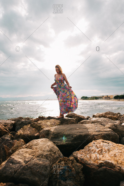 Young redheaded woman wearing colorful dress flowing in the breeze walking along rocky beach