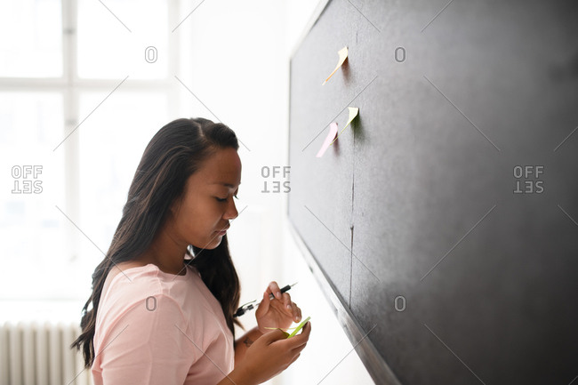Woman writing notes on sticky paper and putting them on black board