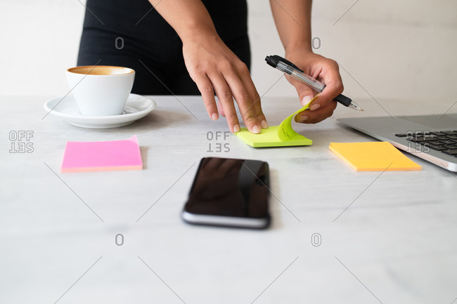 Woman writing notes on sticky paper in an office