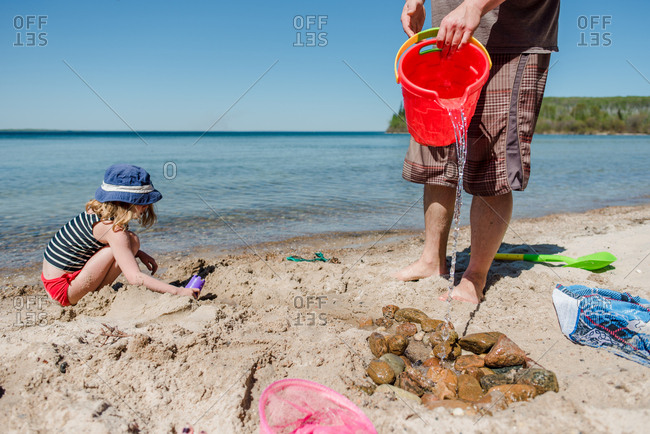 Girl playing in the sand at the beach while her father pours water from a bucket