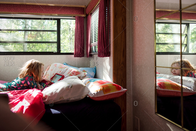 Girl using tablet lying on bed inside recreational vehicle