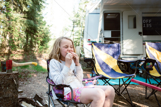 Girl biting into smores at campsite