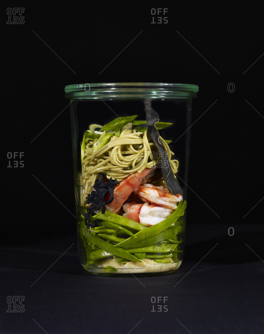 Ingredients for miso soup with shrimp, soba noodles, and green tea leaves in a cup