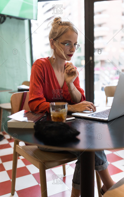 Young vintage girl with a red skirt working with her laptop in a coffee bar in the afternoon