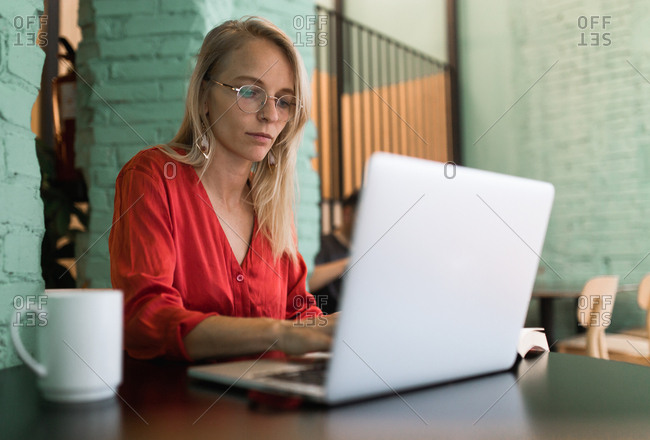 Young vintage girl with a red shirt working with her laptop in a coffee bar in the afternoon