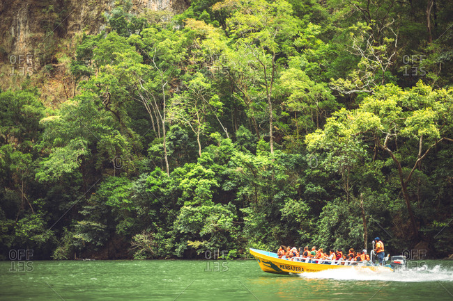 Mexico - March 31, 2018: Group of tourists and guide in life vests floating in motor boat on calm river while travelling through amazing jungle