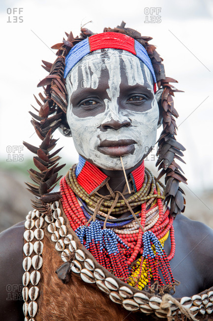 Ethiopia - November, 25, 2014: Crop view of aged black male with beads ornaments around neck and head looking at camera