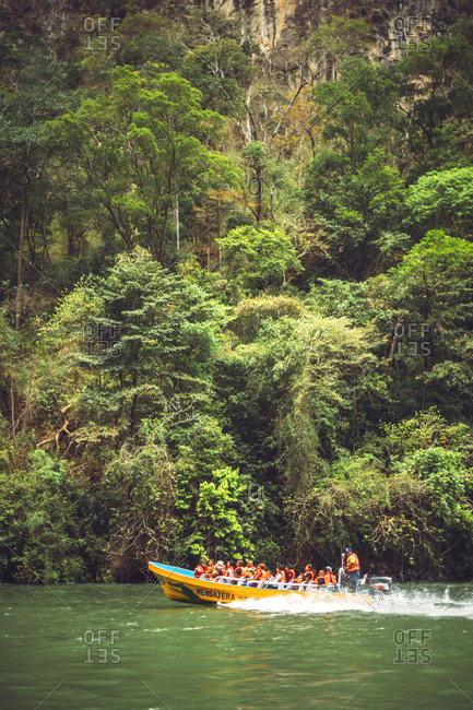 Group of tourists and guide in life vests floating in motor boat on calm river while travelling through amazing jungle