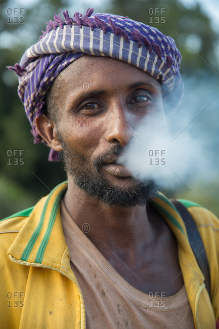 Ethiopia - November, 25, 2014: Crop view of african male in turban and dirty T-shirt smoking and looking at camera