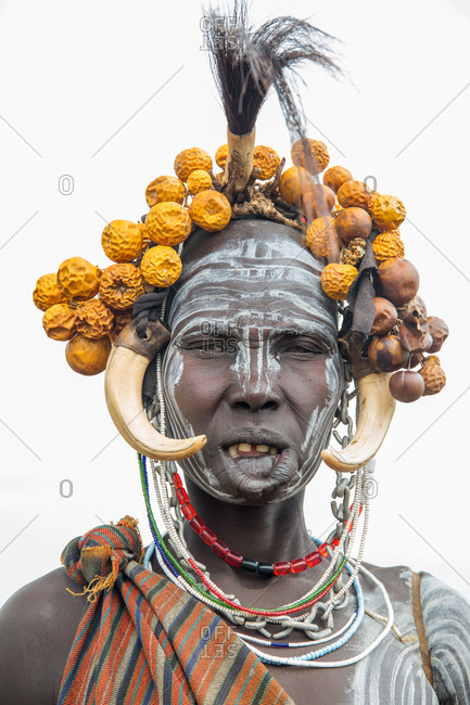Ethiopia - November, 25, 2014: Crop view of african young female with massive clay lip plate and hanging fangs ornaments looking at camera