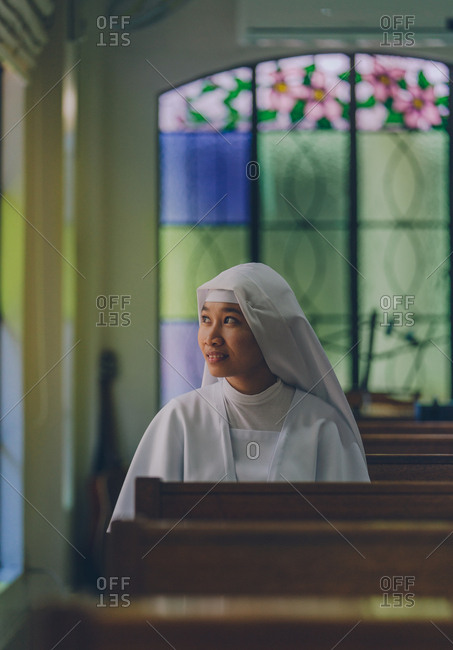 PHILIPPINES, APRIL 16, 2018: Ethnic beautiful woman in white gown of nun sitting on wooden bench in church with colorful windows