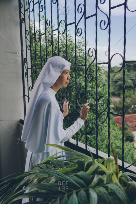 PHILIPPINES, APRIL 16, 2018: cheerful nun in white gowns looking through the fence