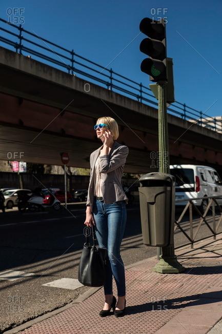Businesswoman talking on phone at traffic light