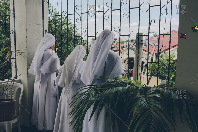 PHILIPPINES, APRIL 16, 2018: Group of cheerful nuns in white gowns looking through the fence