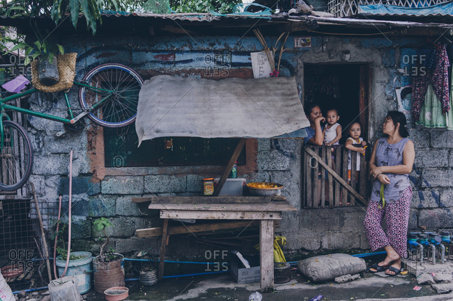 PHILIPPINES, APRIL 16, 2018: Women and kids in window of shabby damaged house with garbage and mess outside in yard