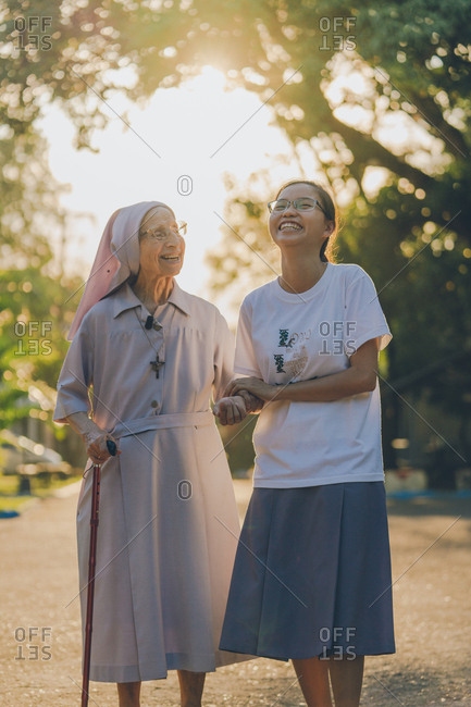 PHILIPPINES, APRIL 16, 2018: Young smiling female holding hand of cute elderly nun with stick on sunlit alley